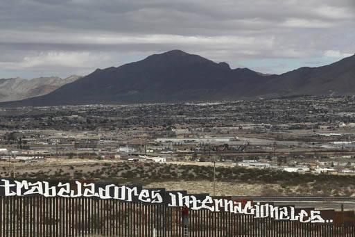 """El poblado de Sunland Park, New Mexico, EEUU se ve al otro lado de la cerca desde Anapra, México y en la cerca se ve una leyenda que en español grafiteado dice: """"Ni ladrones ni narcos; somos tra ..."""