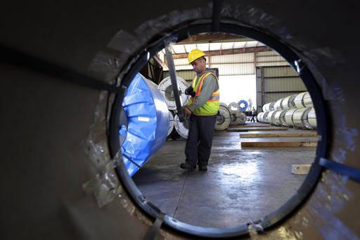 En esta foto de archivo, Nov. 21, 2016, se ve a un obrero mover rollos de lamina de metal en la empresa LMS International, de Laredo, Texas, una de las zonas económicas más dinámicas de la fron ...