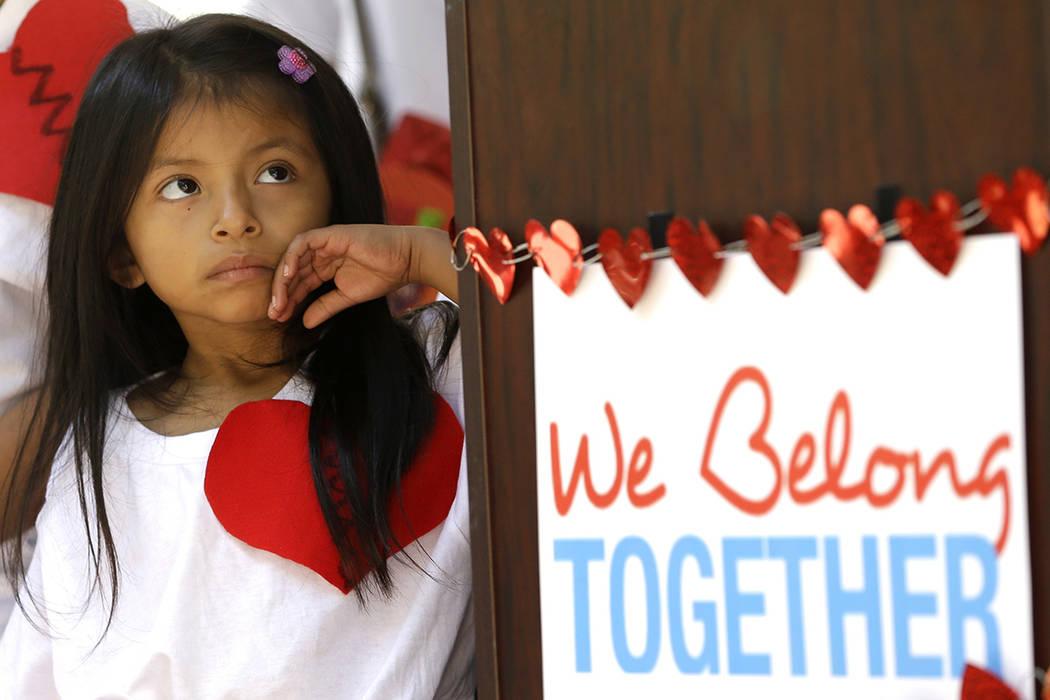 La joven hija de padres inmigrantes ilegales está al lado de un letrero afuera del edificio del condado de Miami-Dade, el martes, 14 de febrero de 2017, en el centro de Miami. Decenas de niños d ...