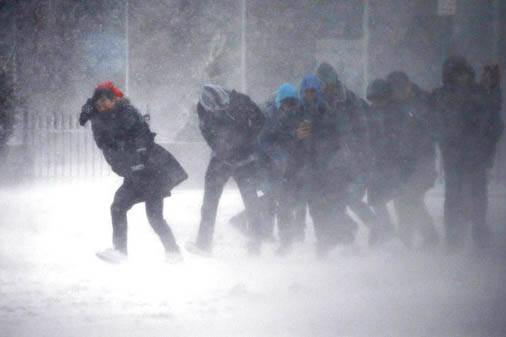 En una calle de Boston este grupo de gente trata de avanzar contra el viento helado, el martes 14 de marzo del 2017. El Servicio Meteorológico Nacional emitió alertas por el mal tiempo para la r ...