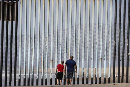Foto de archivo, Marzo 2, 2016. Dos personas caminan en Tijuana, del lado mexicano ante el muro de metal que separa a Mexico con Estados Unidos. (AP Photo/Gregory Bull).