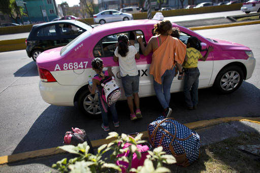 Una mujer guatemalteca con sus cuatro hijos trata el precio del pasaje con un taxista en la Ciudad de México el 25 de enero del 2017. La mujer y sus hijos estuvieron en un albergue para migrantes ...