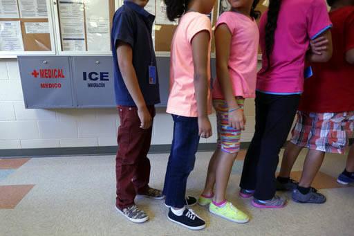 En esta foto de septiembre 10 del 2014 se ve a niños inmigrantes indocumentados detenidos haciendo fila en la cafetería de un Centro Residencial Temporal para mujeres y niños indociumentados de ...