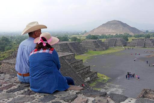 """En esta foto de archivo, de julio 27 del 2016, una pareja sentada en la cúspide de la """"Pirámide de la Luna"""" domina la vista de la plaza central del centro arqueológico Teotihuacan, en el estado ..."""