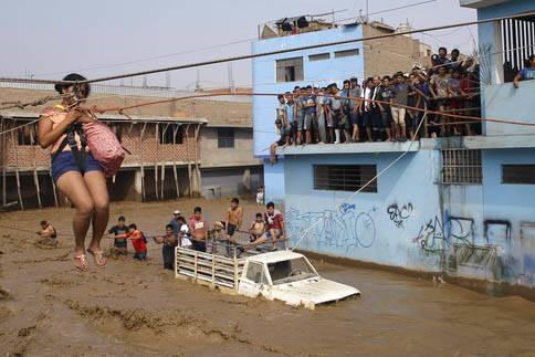 Mientras una muchedumbre atrapada observa, una mujer es rescatada con cuerdas y arnés en un lugar de Lima, Perú, el 17 de marzo del 2017 durante las lluvias torrenciales que azotaron al país. ( ...