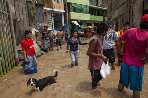 La gente busca recuperar algunas pertenencias de sus hogares inundados en Lima, Perú, el 16 de marzo del 2017. Las lluvias torrenciales de varios días causaron estragos en una ciudad donde no su ...
