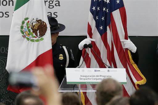 Foto de archivo, de enero 12 del 2016. Oficiales de Patrulla Fronteriza arreglan las banderas de México y Estados Unidos durante un evento binacional de inspección de vehículos circulando en la ...