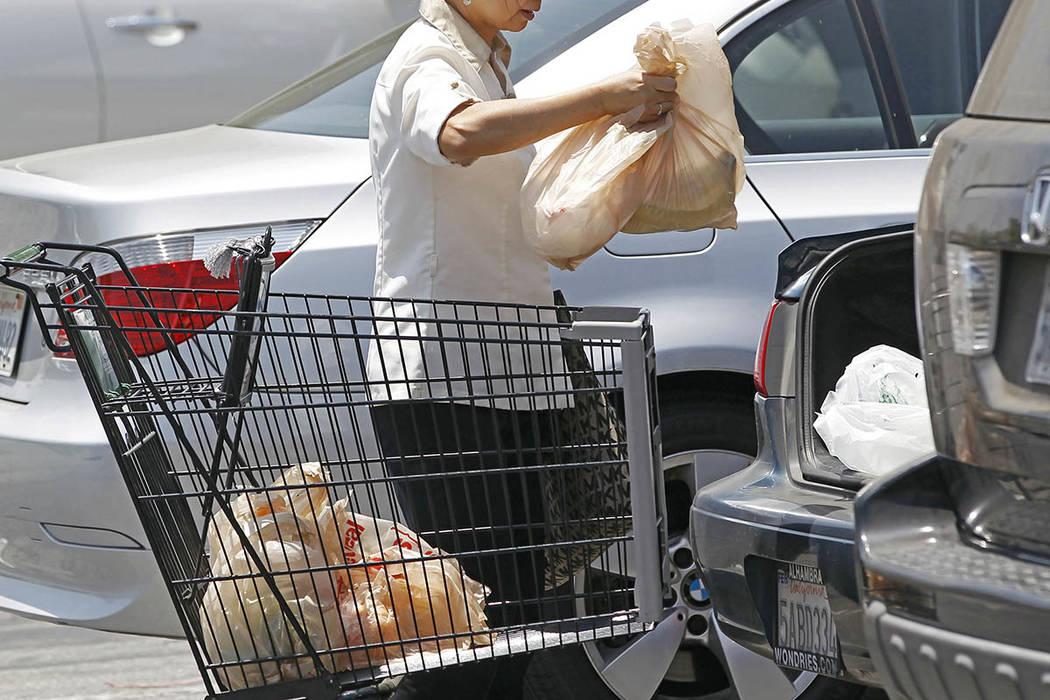 Una mujer guarda en la cajuela de su auto las bolsas de plástico con la mercancía comprada en un supermercado. Propuestas legisativas en Nevada, dadas a conocer en marzo del 2017, podrian prohib ...