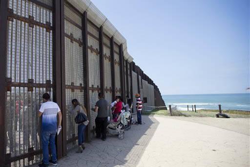 En esta foto de archivo, de Mayo 1, 2016, Eva Lara, segunda desde la izquierda, saluda a través de las rejas a su abuela  Juana Lara quien está del lado de Tijuana México, en la frontera. Eva L ...