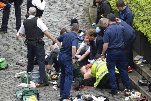 El miembro del Parlamento, Tobias Ellwood, al centro, ayuda a atender a una persona herida afuera del Parlamento en Londres, Inglaterra, el 22 de marzo del 2017, cuando un ataque terrorista dejó  ...