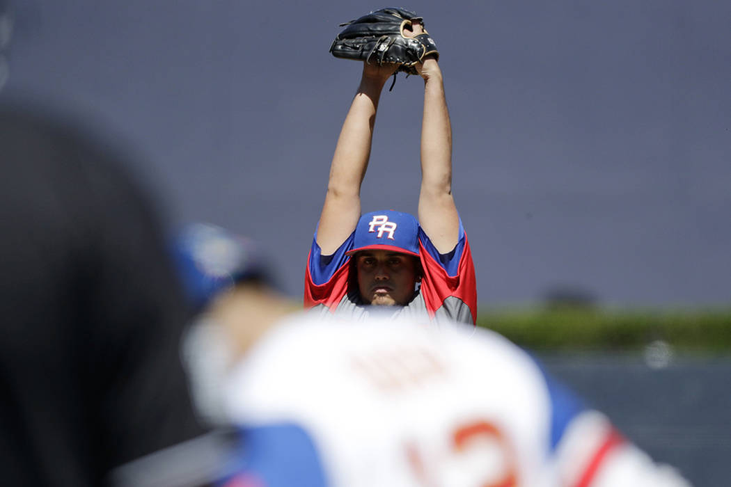 Puerto Rico pitcher Jose De Leon stretches as he pitches to Venezuela's Rougned Odor during the first inning of a second-round World Baseball Classic baseball game Saturday, March 18, 2017, in San ...