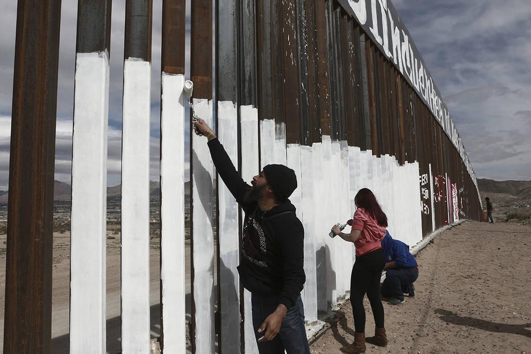 """Los manifestantes pintan la cerca de la frontera debajo de un lema recién terminado que dice """"ni delincuentes ni ilegales, nosotros somos trabajadores internacionales"""" en Ciudad Juárez, México, ..."""