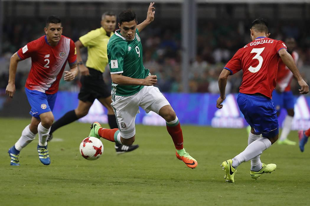 El mexicano Raúl Jiménez, centro, va con la pelota, entre el costarricense Johnny Acosta, a la izq., y Giancarlo González durante un partido de eliminatoria rumbo a la Copa Mundial de Rusia 201 ...