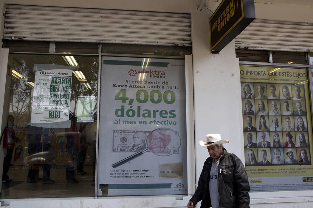 Un hombre recorre los carteles anunciando servicios de transferencia de dinero y préstamos fuera de un negocio en la Ciudad de México, el martes 5 de abril de 2016. El candidato republicano a la ...