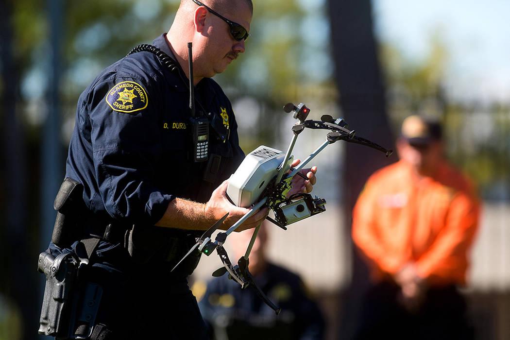 El subdirector del Sheriff del Condado de Alameda Dave Durbin, izq., opera un drone mientras demuestra una operación de búsqueda y rescate, el viernes 14 de agosto de 2015 en Dublín, California ...