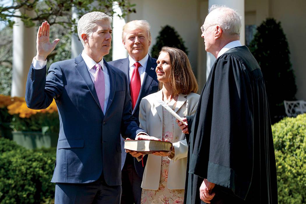 El presidente Donald Trump observa cómo el juez de la Corte Suprema, Anthony Kennedy administra el juramento judicial al juez Neil Gorsuch en el Jardín de las Rosas de la Casa Blanca, el lunes 1 ...