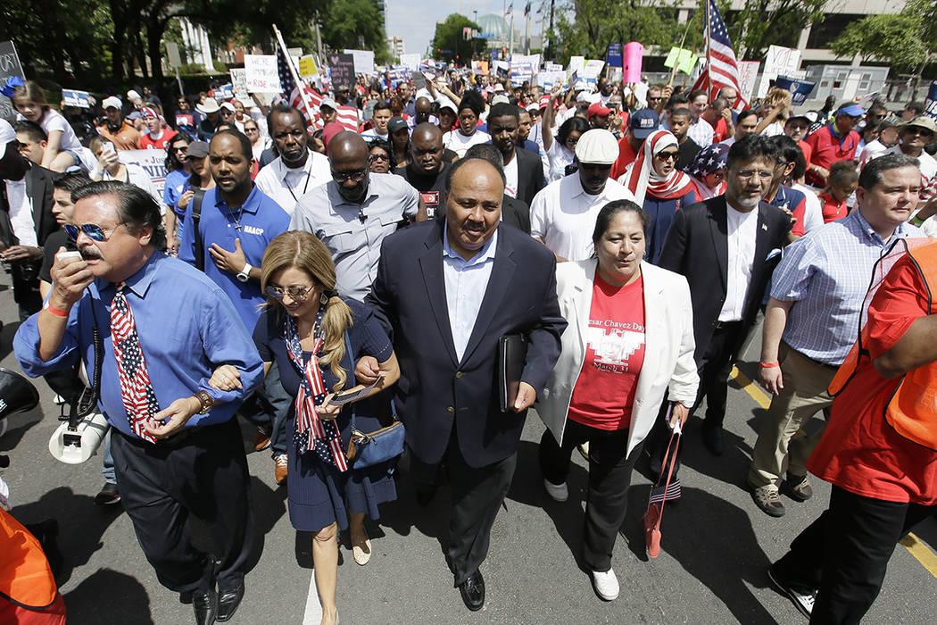 Martin Luther King III, centro, ayuda a llevar una marcha de protesta con otros activistas por el centro de Dallas, el domingo 9 de abril de 2017. Miles de personas marchan y se están reuniendo e ...