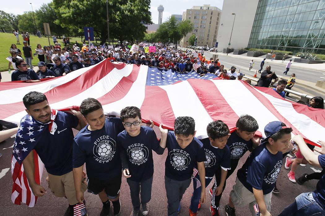 Jóvenes y adultos llevan una bandera americana durante una marcha de protesta por el centro de Dallas, el domingo 9 de abril de 2017. Miles de personas están marchando y reuniéndose en el centr ...