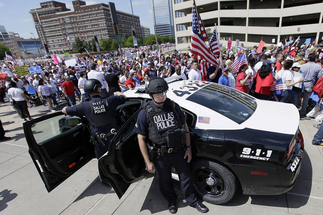 La policía de Dallas vigila durante una marcha de protesta por el centro de Dallas, el domingo 9 de abril de 2017. Miles de personas marchan y se reúnen en el centro de Dallas para pedir una rev ...