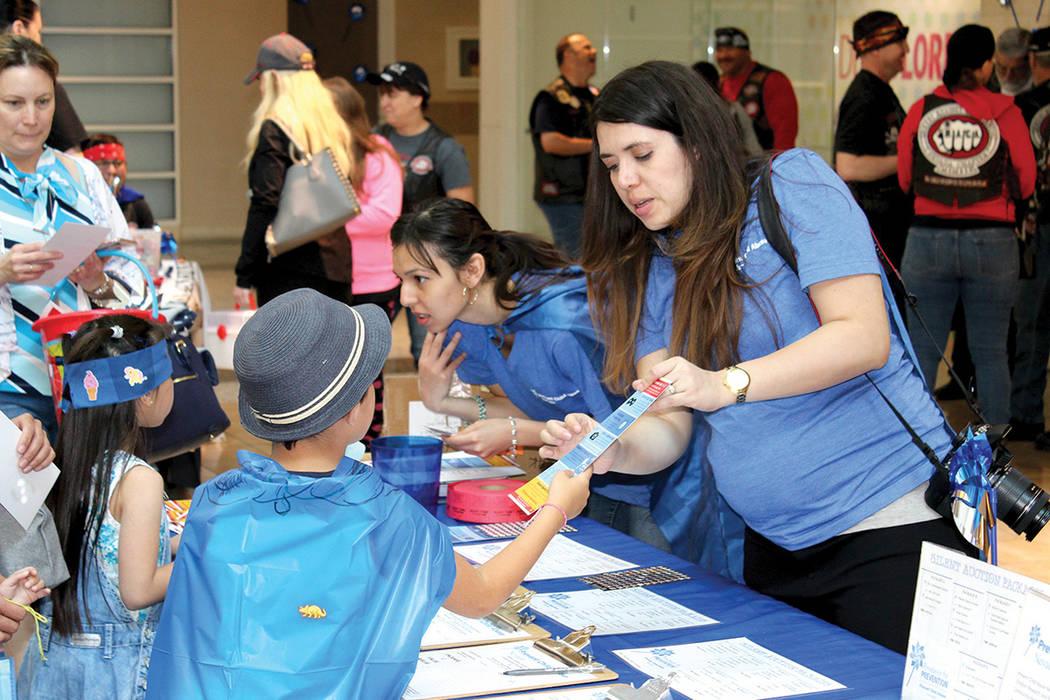 La coordinadora del programa PCA, Valeria Gurr, explica a un niño sobre cómo cuidarse de un abuso, durante el evento de prevención de abuso infantil realizado en Galleria Mall, el sábado 8 de  ...