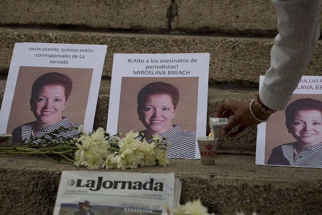 Una mujer enciende una vela junto a las fotos del periodista mexicano Miroslava Breach, abatido el jueves en el norteño estado de Chihuahua, en un altar improvisado durante una manifestación en  ...