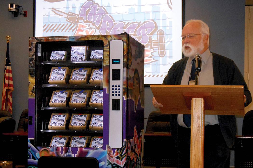 """El Dr. Joe Iser, Jefe del Distrito de Salud del Sur de Nevada, al momento de dar a conocer el programa piloto """"Impact Exchange"""". A su lado una de las máquinas expendedoras de jeringas para ad ..."""