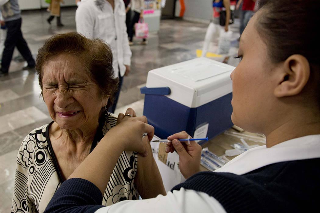 Constanza Fuentes recibe vacunación voluntaria contra la gripe por parte de la enfermera Carla Flores en una estación de metro de la ciudad de México, el lunes 27 de enero de 2014. Las autorida ...