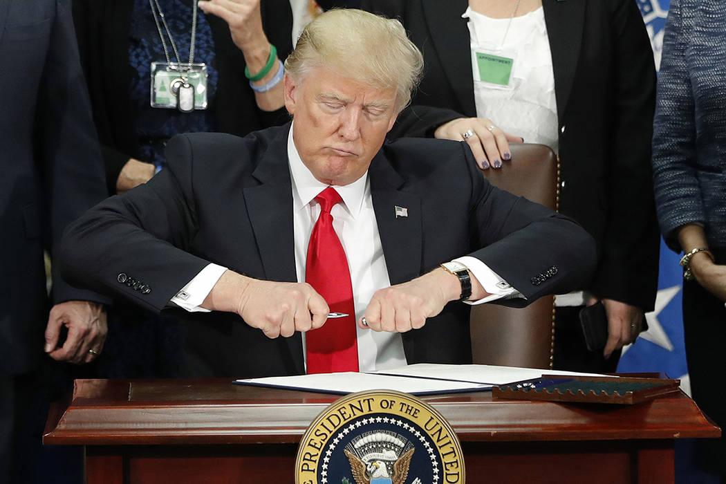 En esta foto de archivo del 25 de enero de 2017, el presidente Donald Trump saca la tapa de una pluma antes de  rmar la orden ejecutiva para las medidas de inmigración para construir muro fronter ...