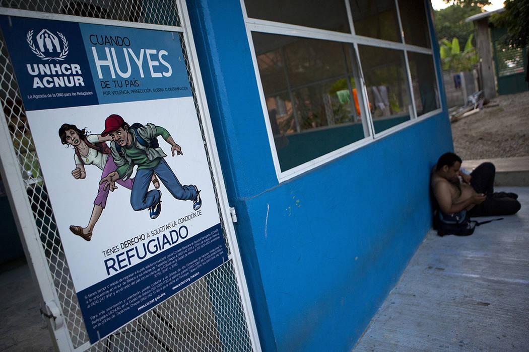 ARCHIVO- En esta foto del 6 de diciembre de 2016, un hombre descansa cerca de un cartel que informa a los migrantes que si huyen de la violencia, la persecución, la guerra o la discriminación, t ...
