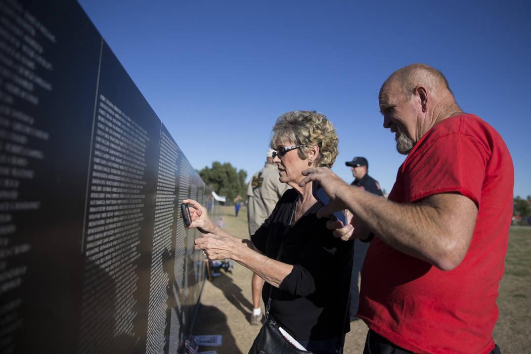 Lisa Mains, a la izquierda, y su esposo Robert, toman una foto del nombre de un amigo en la réplica de la Muro de los Veteranos de Vietnam que fue presentada por el Veterans Traveling Tribute en  ...