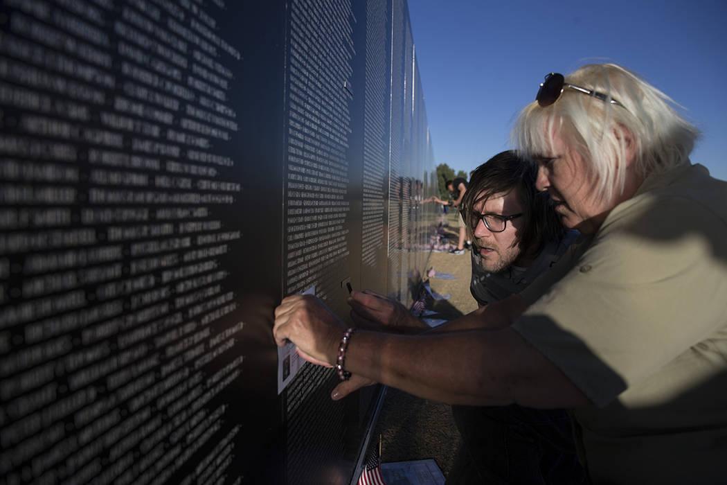"""El veterano del Ejército de los Estados Unidos, Gayle """"Stormy"""" Patrick, con su hijo Jordan Meyers, grabó el nombre de su tío en la réplica de la muralla conmemorativa de los Veteranos de Vietn ..."""