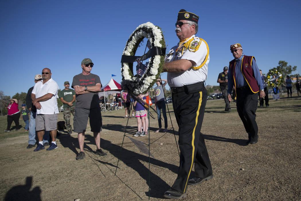 Neil Johnson, centro, presidente de Vietnam Veterans of America Capítulo 1076, presenta la guirnalda de prisionero de guerra durante la ceremonia de apertura de la réplica de la Muro de los Vete ...