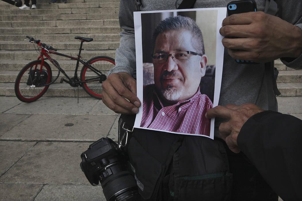 Un periodista reúne una fotocopia del colega Javier Valdez durante una protesta para llamar la atención sobre la última ola de asesinatos de periodistas, en el Ángel de la Independencia en la  ...