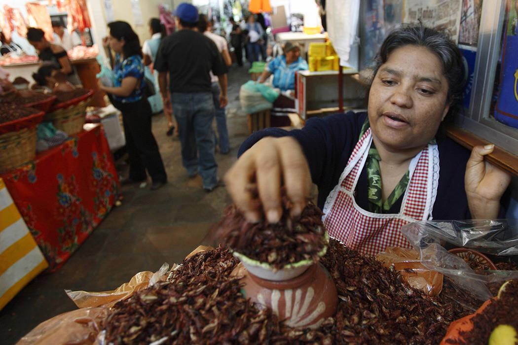 ARCHIVO- Peta Ruiz vende una delicadeza local de saltamontes bañados en polvo de chile y sal en el mercado de la ciudad de Oaxaca, México, el martes 8 de enero de 2008. Más de un año después  ...