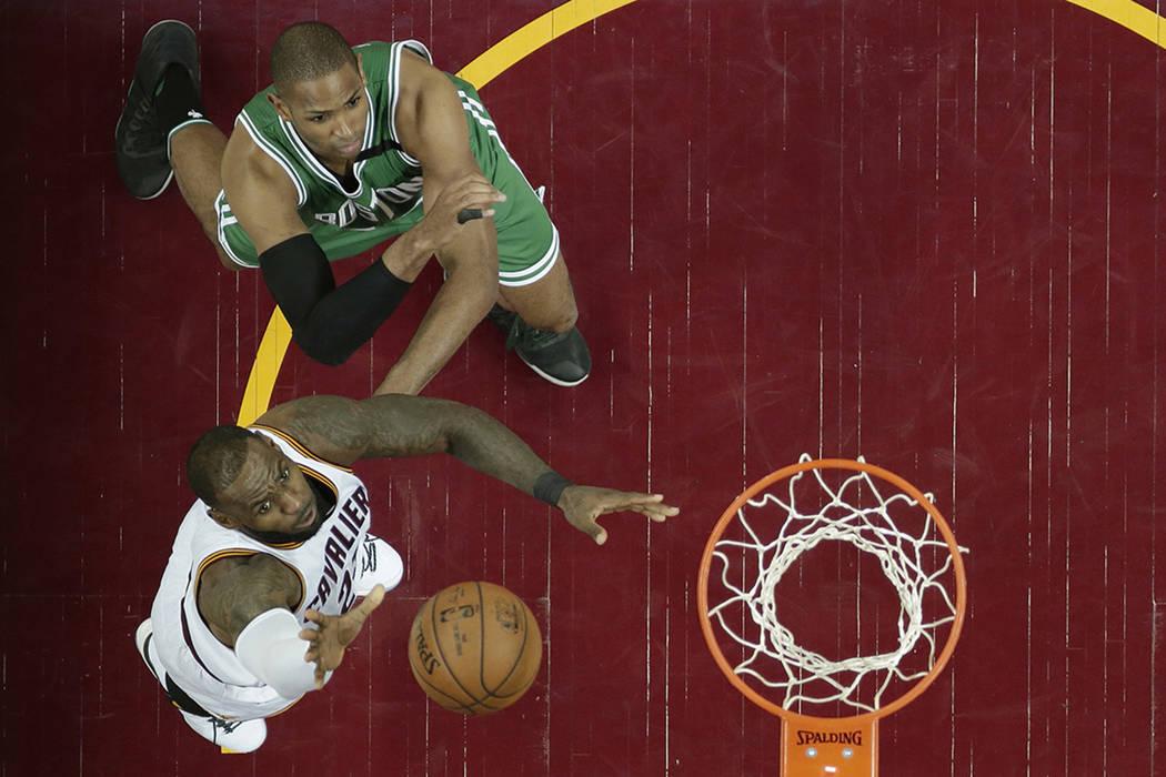 LeBron James de Cleveland Cavaliers, a la izquierda, conduce a la canasta contra Al Horford, de Boston Celtics, de República Dominicana, en la segunda mitad del cuarto partido de la final de la C ...