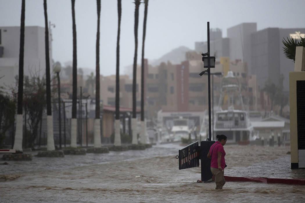 ARCHIVO- Una mujer atraviesa una calle inundada por las fuertes lluvias provocadas por el huracán Newton en Cabo San Lucas, México, el martes, 6 de septiembre de 2016. El Centro Nacional de Hura ...