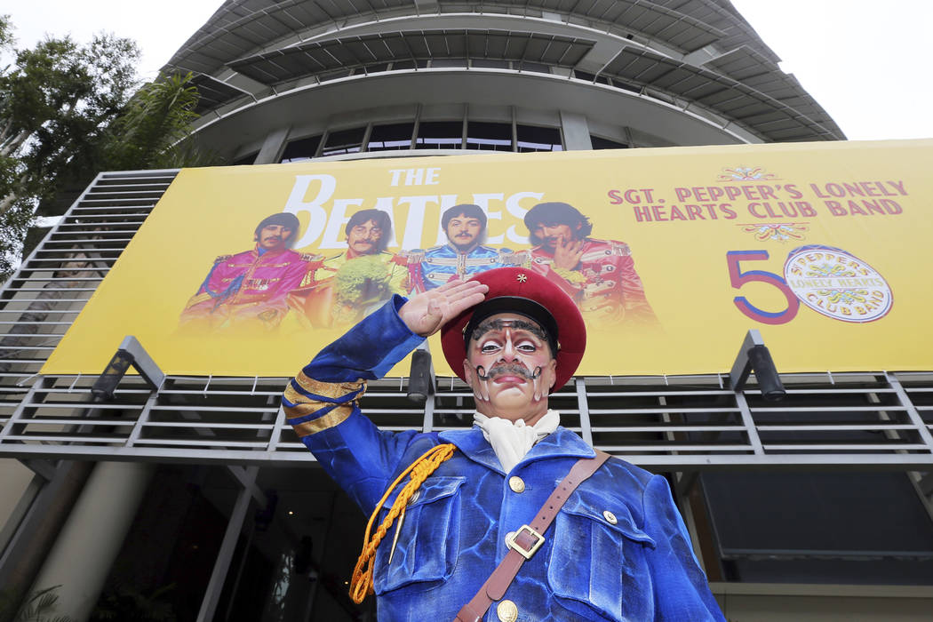 """Un actor del Cirque du Soleil que retrata al Sgt. Pepper saluda después de levantar una bandera conmemorativa en el 50 aniversario del clásico álbum de los Beatles, """"Sgt. Pepper's Lonely Hearts ..."""