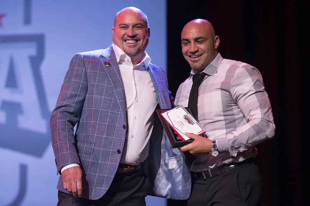 Tony Sánchez, entrenador de fútbol de UNLV, presenta el premio al mejor jugador de fútbol del año a su hermano Kenny Sánchez, entrenador del equipo de fútbol de Bishop Gorman, en representac ...
