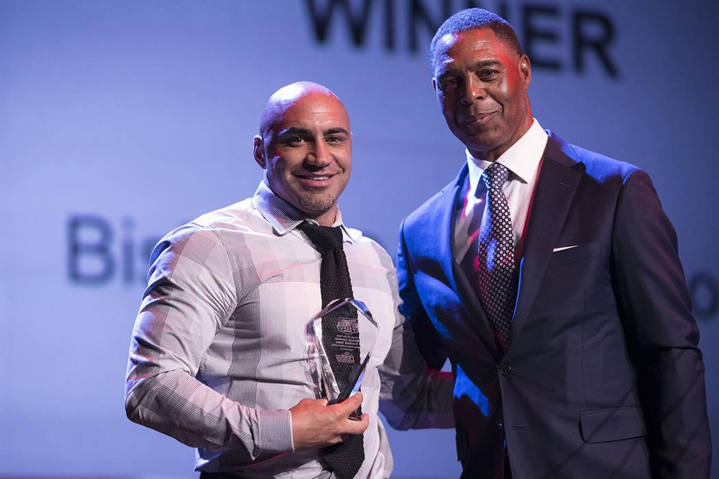 Kenny Sanchez, entrenador en jefe del equipo de fútbol Bishop Gorman High School, es presentado con el premio al equipo del año por la sala de fútbol del famoso Marcus Allen durante el premio a ...
