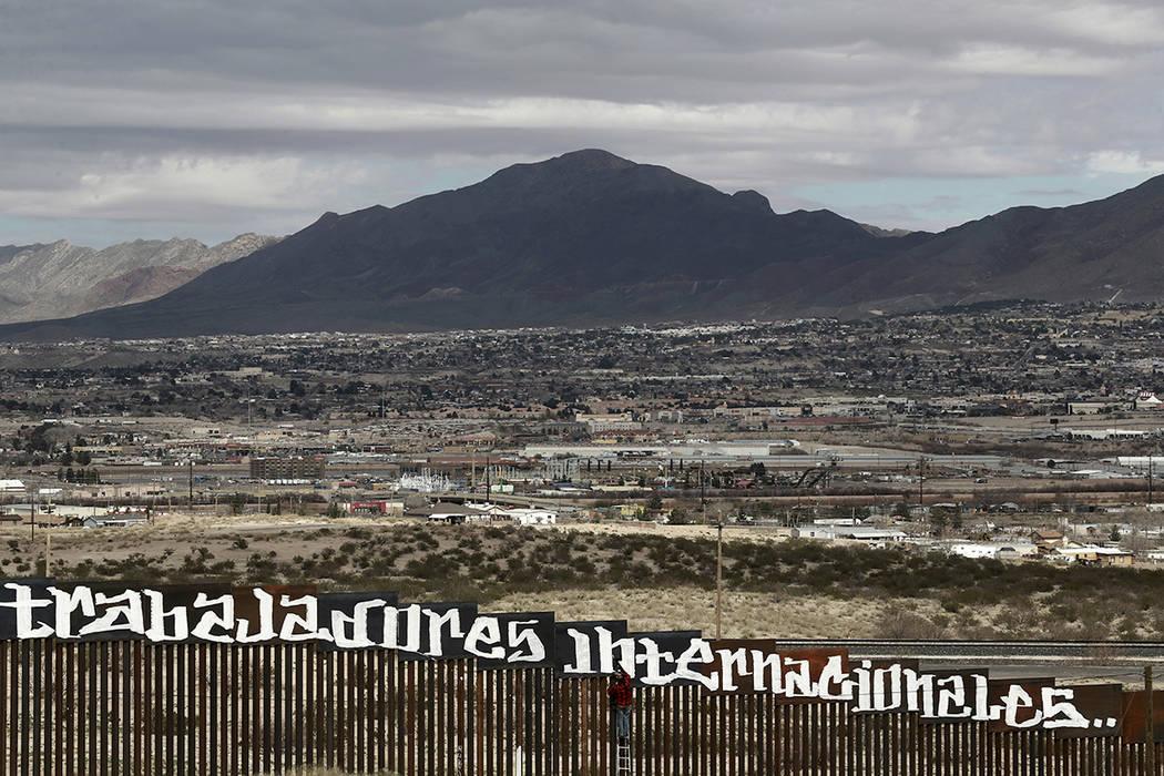 """Sunland Park, Nuevo México, es visto por encima de la valla fronteriza de Estados Unidos cuando un manifestante termina de pintar el lema español """"Ni los delincuentes ni los ilegales, nosotros s ..."""