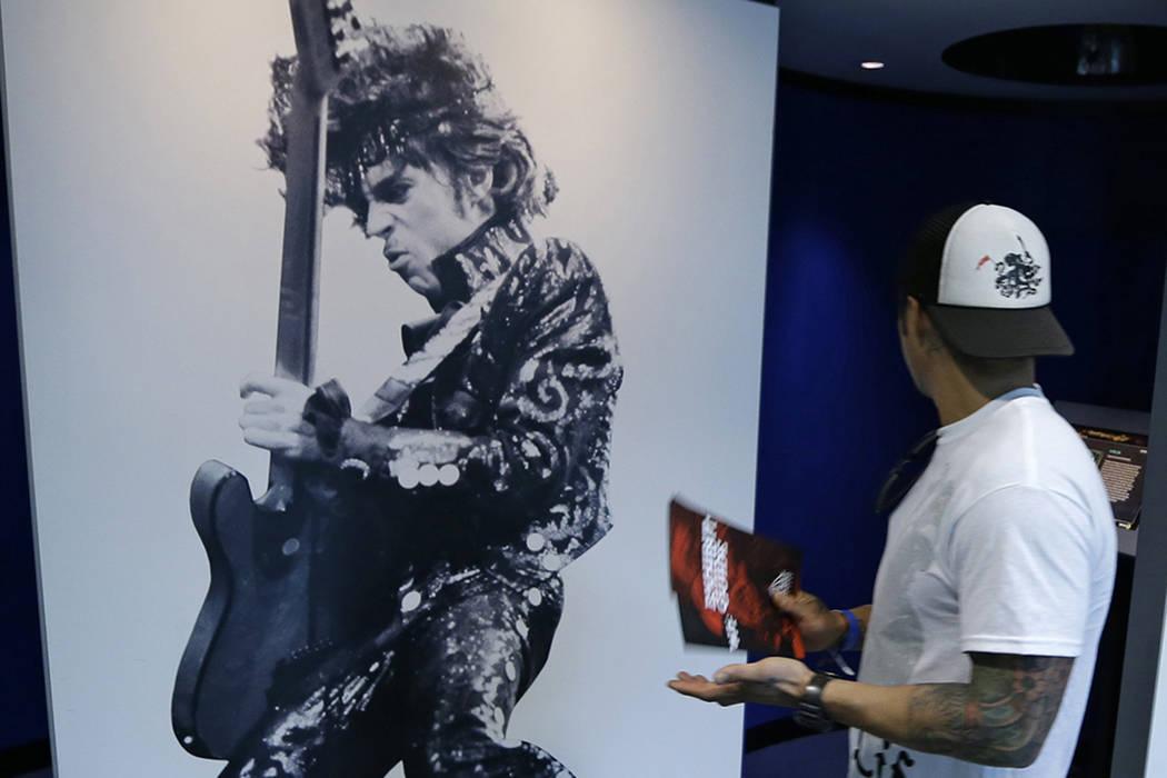 Un hombre camina por un mural del príncipe en el salón de la fama y del museo del rock and roll, viernes, 22 de abril de 2016, en Cleveland. La estrella del pop murió el jueves a la edad de 57  ...