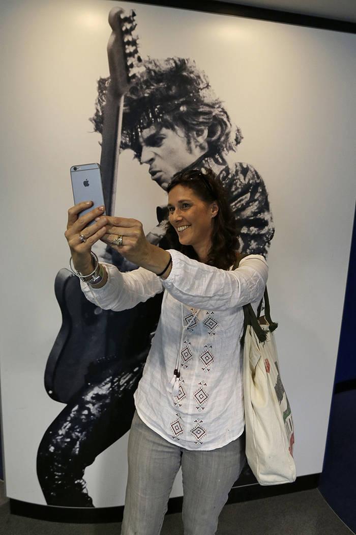 Marcie Carrier lleva un selfie con un mural de Prince en el Salón de la Fama y el Museo del Rock and Roll, el viernes 22 de abril de 2016, en Cleveland. La estrella del pop murió el jueves a la  ...