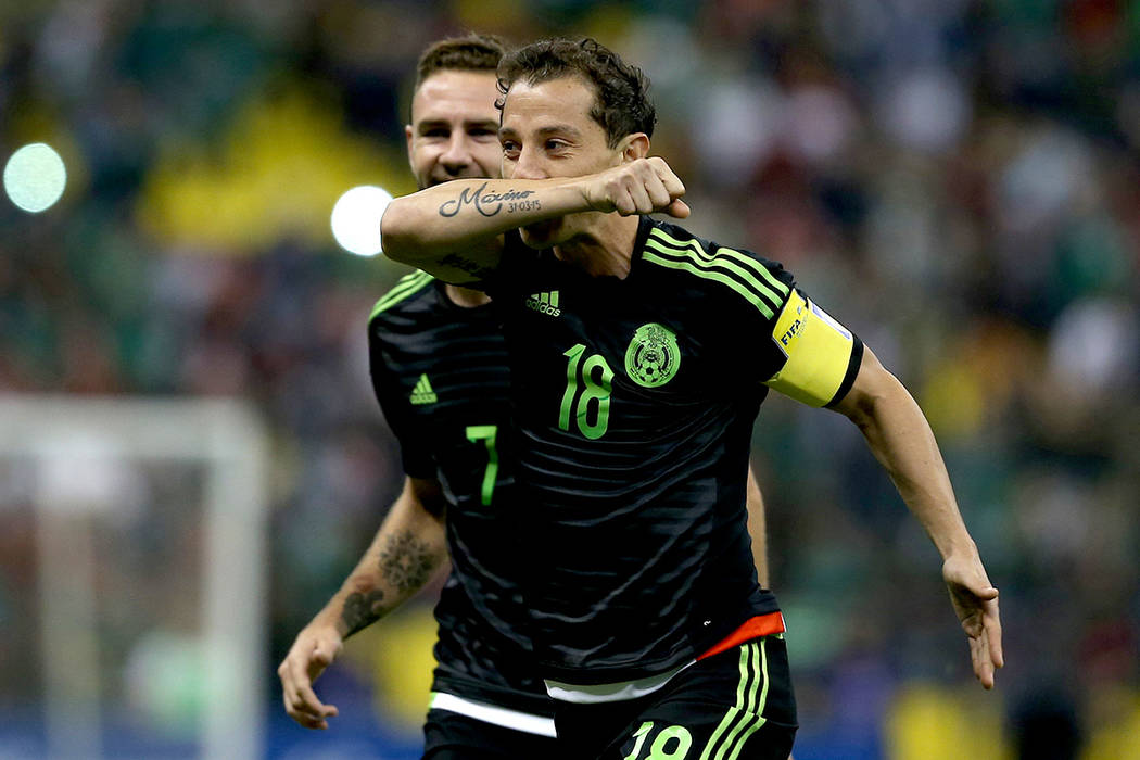 ARCHIVO- El mexicano Andrés Guardado, a la derecha, celebra, seguido por su compañero de equipo Miguel Layun tras anotar contra El Salvador, durante un partido de fútbol de clasificación para  ...