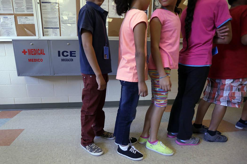 ARCHIVO- En esta foto de archivo del 10 de septiembre de 2014, los niños inmigrantes detenidos se alinean en la cafetería del Centro Residencial del Condado de Karnes, un hogar temporal para muj ...