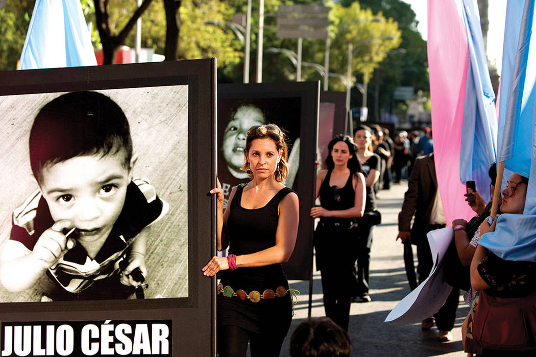 Las mujeres llevan fotografías de niños que murieron en un incendio en 2009 durante una protesta en el cuarto aniversario del incendio en la Ciudad de México, el miércoles 5 de junio de 2013.  ...