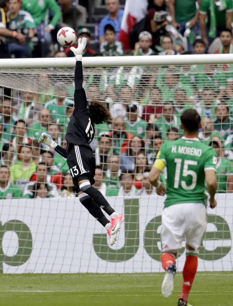El guardameta mexicano Guillermo Ochoa intenta alcanzar el balón cuando los estadounidenses Michael Bradley anoten en el partido de clasificación para el Mundial de Fútbol en el Estadio Azteca, ...