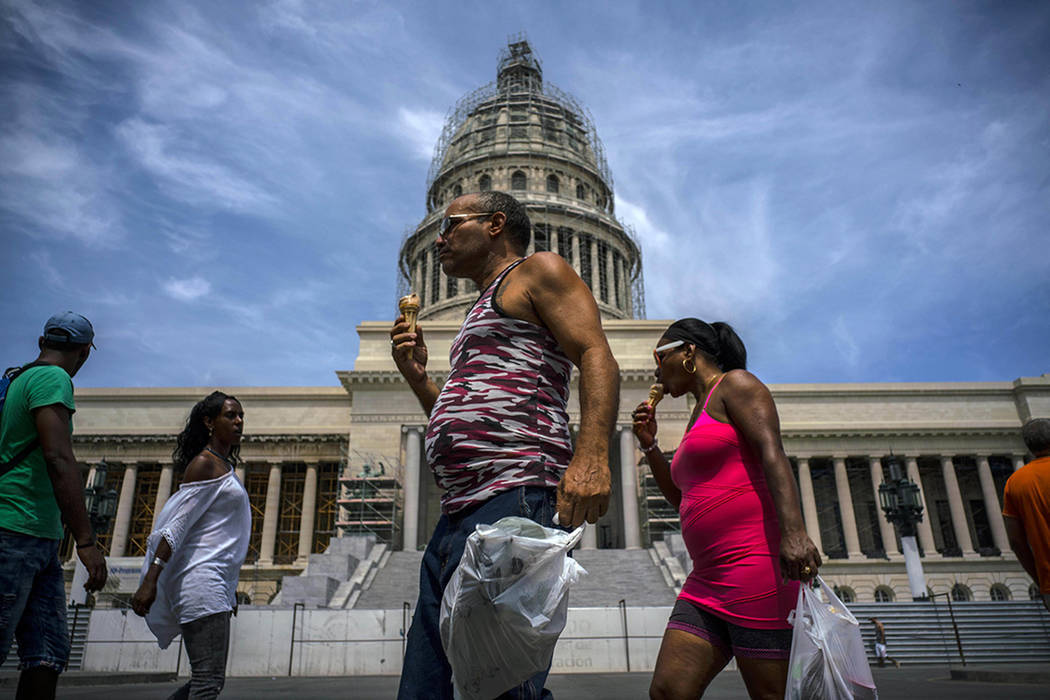 People eating ice cream in front of the Capitolio in Havana, Cuba, Saturday, June 17, 2017. United States President Donald Trump declared he was restoring some travel and economic restrictions on  ...