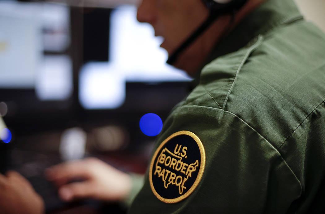 ARCHIVO - En esta foto de archivo del 5 de junio de 2014, un agente de la Patrulla Fronteriza utiliza un auricular y una computadora para realizar una entrevista de larga distancia por video desde ...