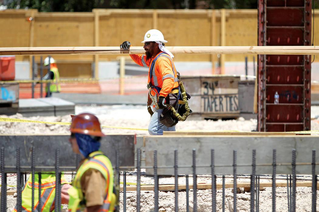 ARCHIVO- Un trabajador de construcción mueve tableros después de una presentación organizada por el Grupo de Construcción PENTA sobre los peligros de seguridad en temporada de calor. Lunes 1 d ...