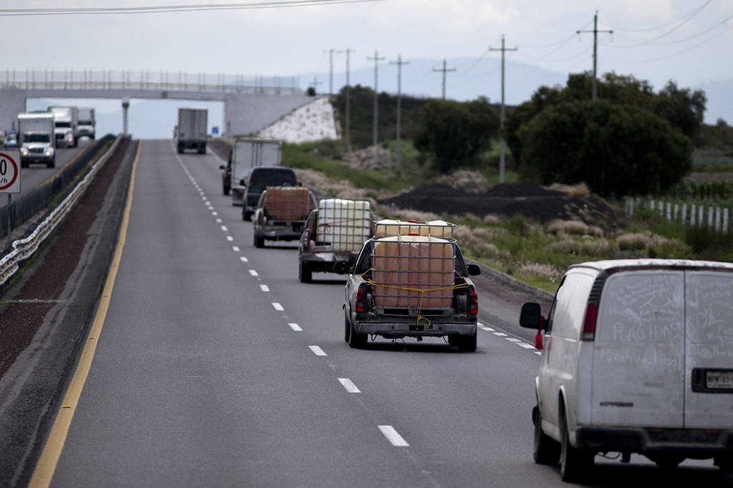 En esta foto del 11 de julio de 2017, los camiones que llevan contenedores llenos de gasolina robada son conducidos por la policía y el ejército a un lugar seguro cerca de Tepeaca, México. Las  ...